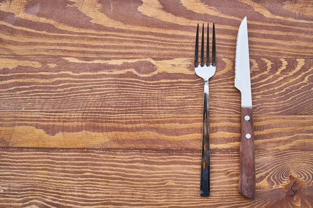木のテーブルに乗ったフォークとナイフ