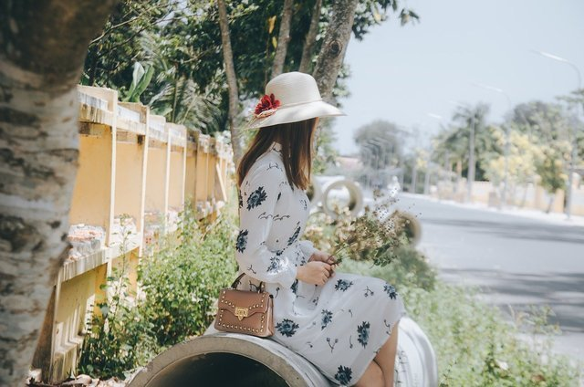 白い帽子を被って待つ女性