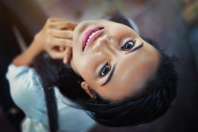 リップを塗って笑顔で見上げる女性