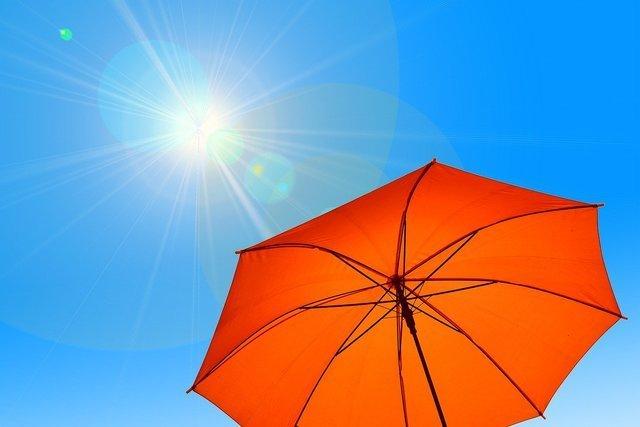 強い日差しとオレンジのパラソル