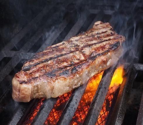 強火の網で焼かれているステーキ