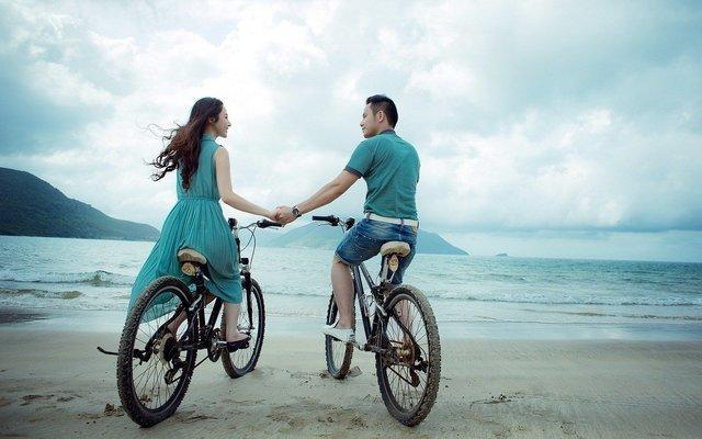 手を繋いで海辺で自転車に乗る男女