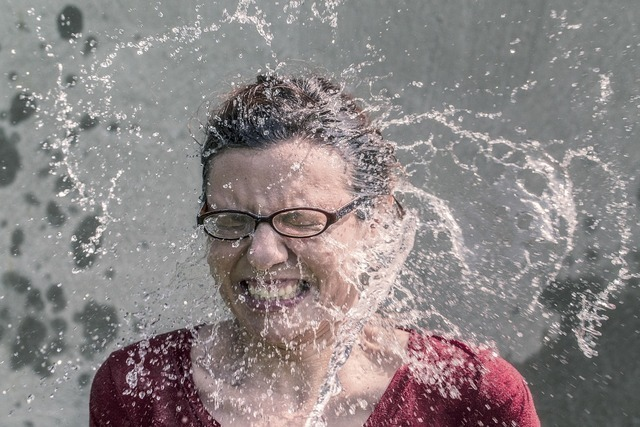 水をかけられるメガネの女性