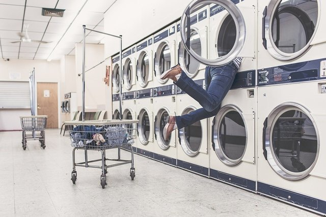 洗濯機に頭を突っ込む女の人