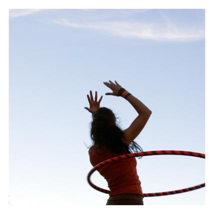 空を背景にフラフープを回す女性