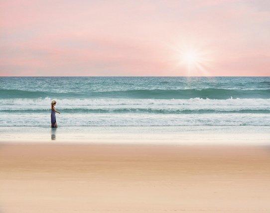朝方の海岸を歩く人