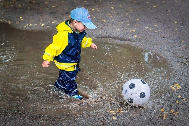水溜りでサッカーをする子供
