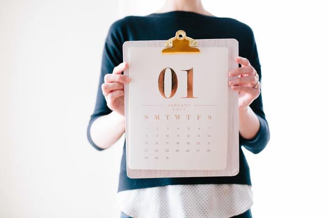 クリップボードカレンダーを持つ女性