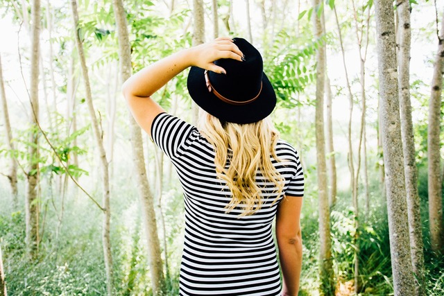 帽子を触る女性
