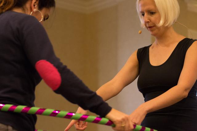 フラフープの回し方を教える女性