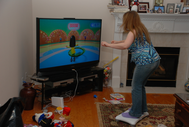 フラフープを回すゲームをする女性