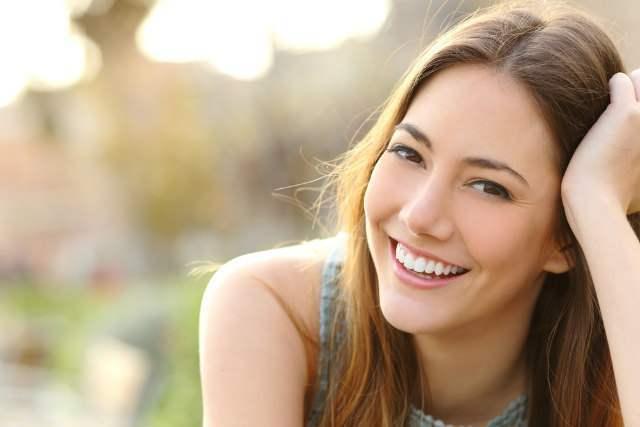 微笑むグレーのタンクトップの女性