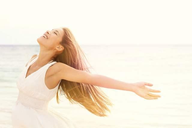 海辺で風を楽しむ女性