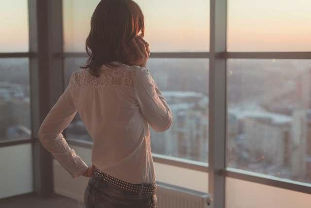 窓の外の夕景色を見る女性の後ろ姿