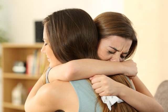涙を流しながら抱き合う女性
