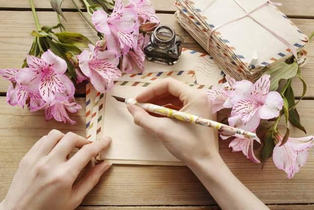 花と封筒を用意して便箋に手紙を書く女性画像