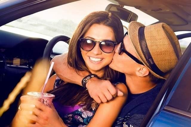 女性を後ろから抱きしめてキスする男性