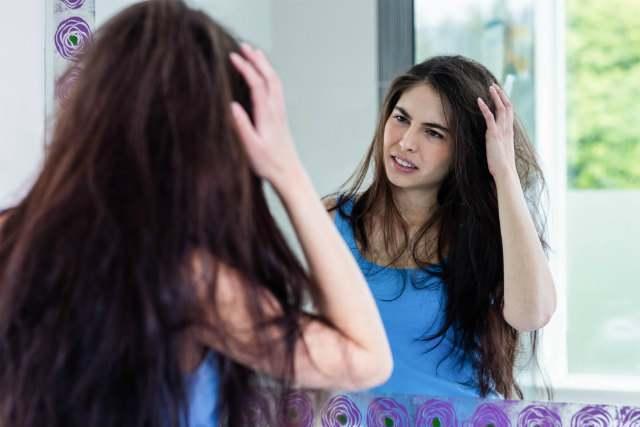 鏡の前で髪をいじっている女性