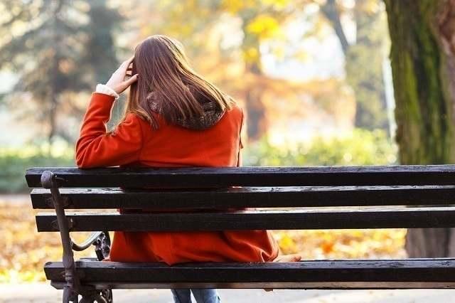 ベンチに座る赤いコートを着た女性
