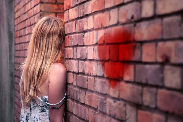 壁にたたずむ女性