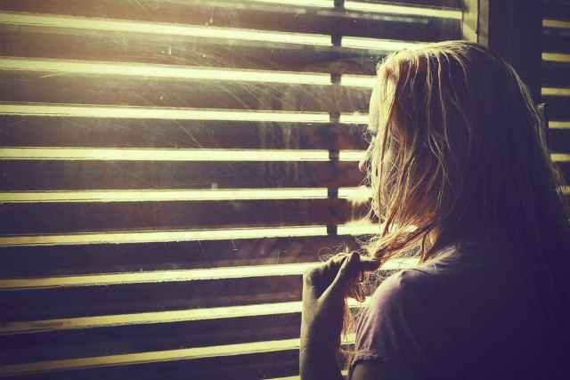 暗い部屋で窓際に立つ女性