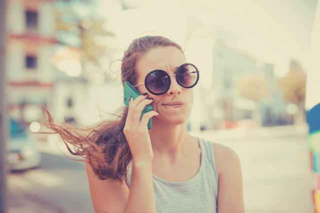 電話をしながら顔をしかめる女性