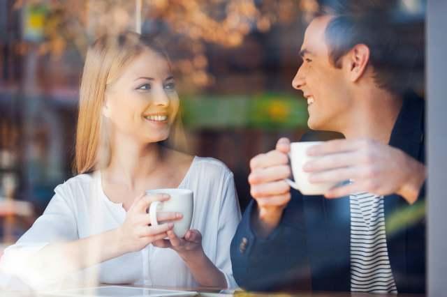 窓際の席で微笑むカップル画像