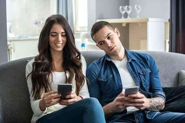 女性の携帯を男性が覗き見している画像