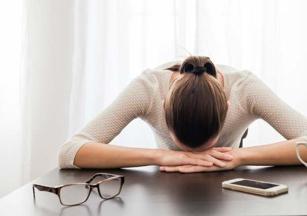机に顔をふせる女性