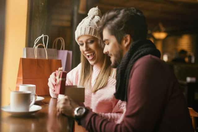 女性にプレゼントを渡す男性とプレゼントを見て喜ぶ女性