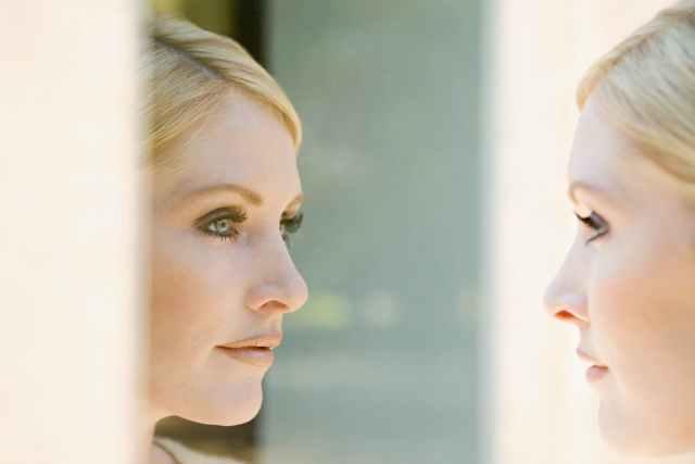 鏡で自分の顔を見る女性