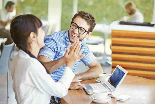 女性の仕事の成功をハイタッチで喜ぶ男性