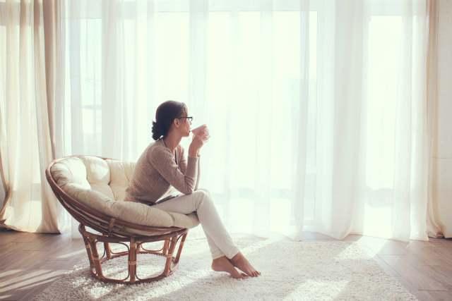 窓を眺めているズボン姿の女性