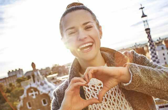 笑顔で手でハートを作る女性画像