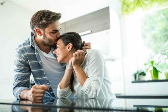男性に優しく抱きしめられながらキスをされる女性