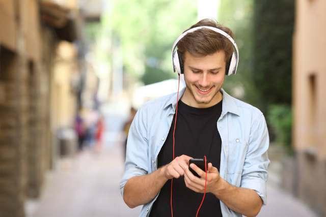 ヘッドフォンで曲を聴く男性
