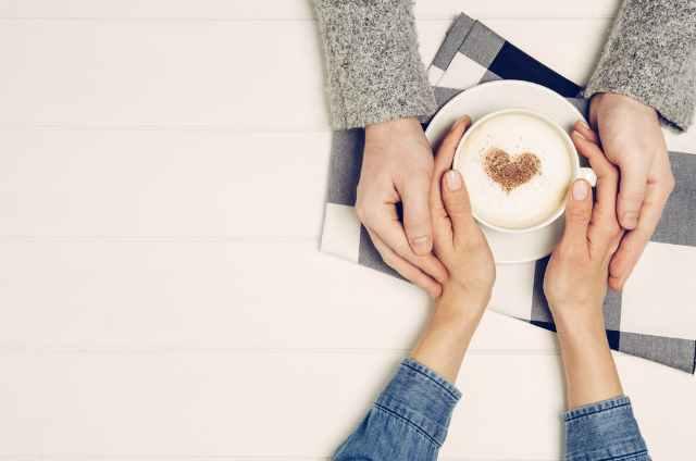 カフェで手を握る男女