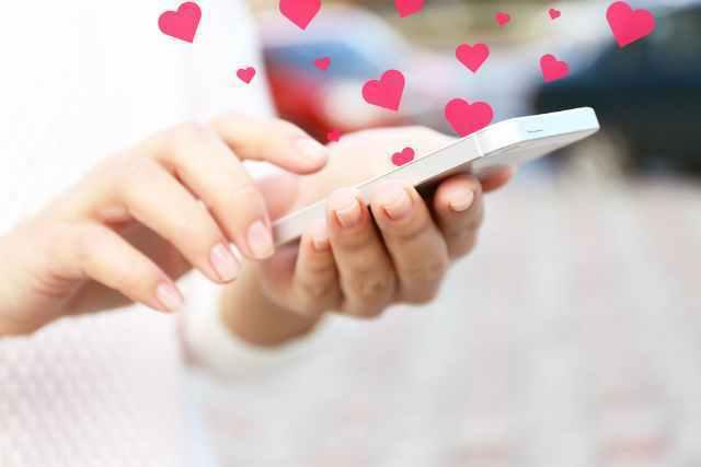 女性が持つ携帯からハートが出ている画像