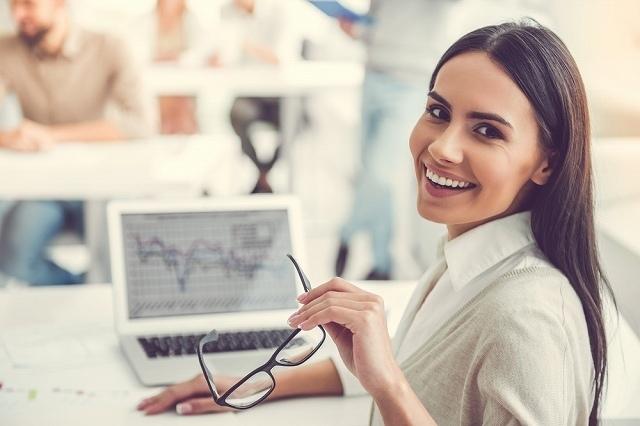 パソコンの前でにこやかに微笑む女性
