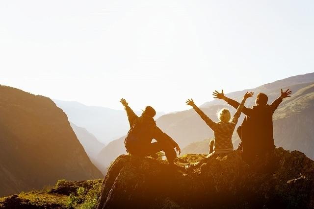 山の上の夕焼けを楽しむ人