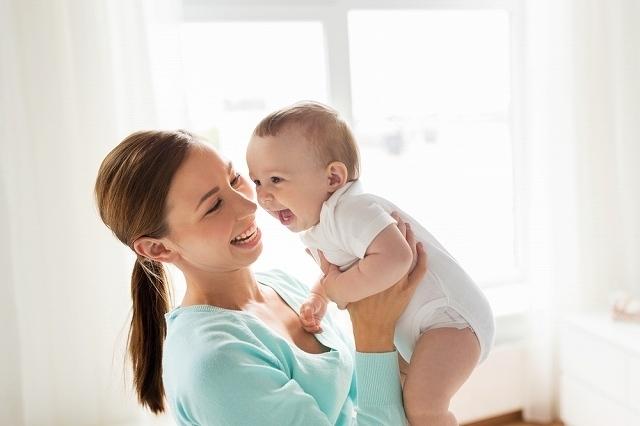 赤ちゃんを抱き上げる女性