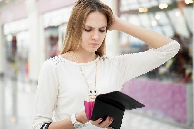 財布の中身を見つめる女性