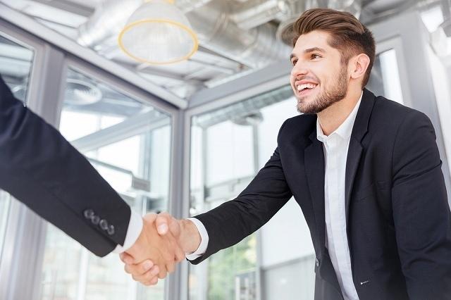 仕事の相手と握手する男性