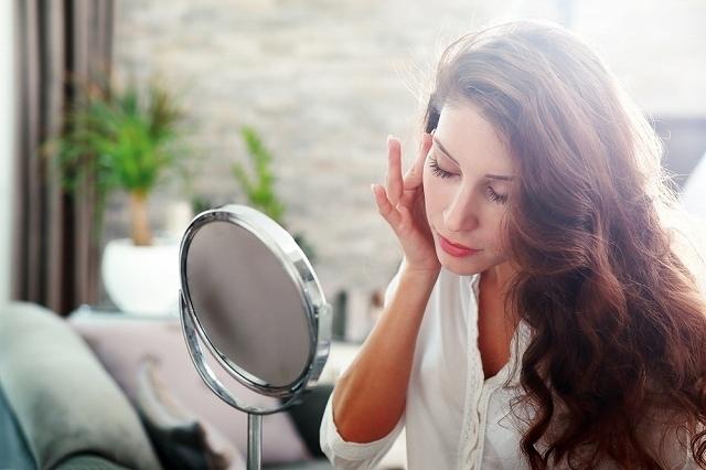 鏡を見ながら肌を触る女性