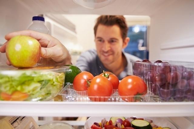 冷蔵庫に手を入れる男性
