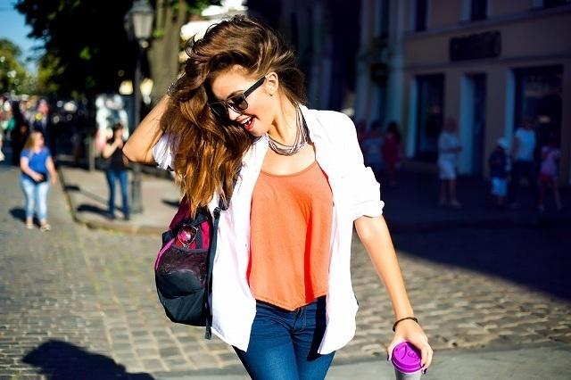 サングラスをかけてカバンを持って歩く女性