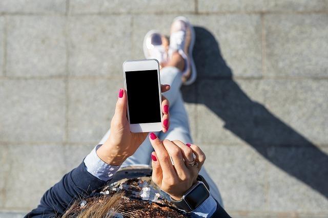 携帯を手に持つ女性