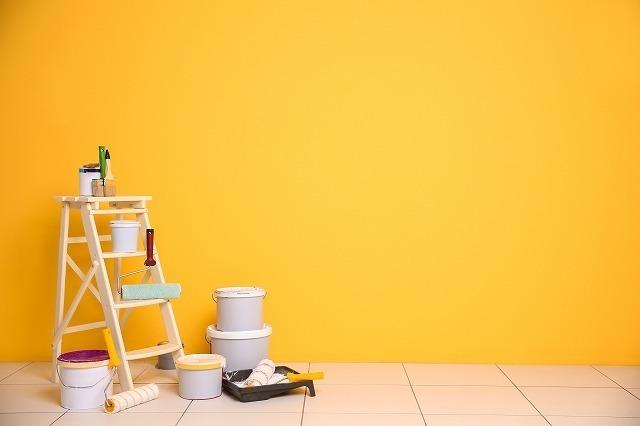 黄色い壁とペンキ缶と脚立