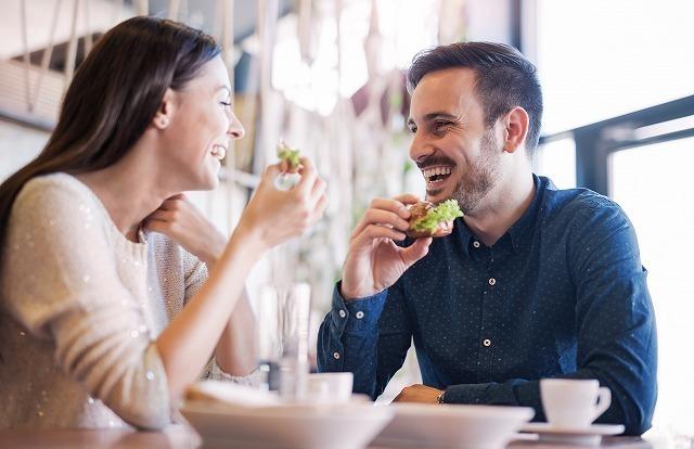 笑顔で食事をする男女