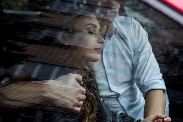 車で女性を抱きしめる男性